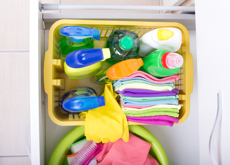 stored: Top view of cleaning supplies and equipment stored in drawer in kitchen cabinet. House cleaning and storing concept
