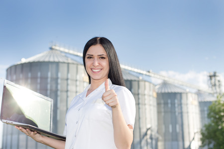 agronomist: Young woman agronomist in white coat standing with laptop in front of grain silo and showing ok sign with thumb up Stock Photo