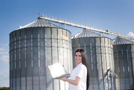 agronomist: Young woman agronomist in white coat standing with laptop in front of grain silo