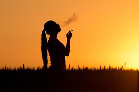 Silhouet van de jonge vrouw het roken van sigaretten bij zonsondergang in een tarweveld