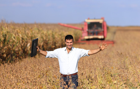 landowner: Happy young landowner with raised arms and laptop standing on soybean field during harvest