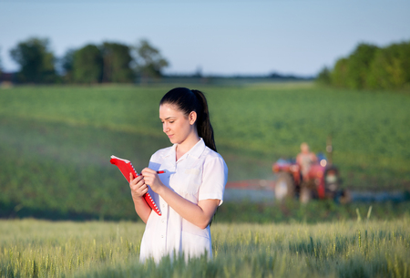 agronomist: Young pretty agronomist standing in green wheat field and writing notes. Tractor working in background