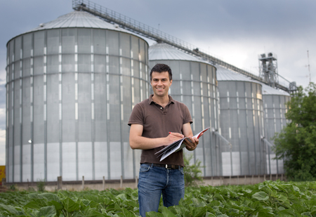 Young attractive farmer standing in sunflower field in front of grain silo