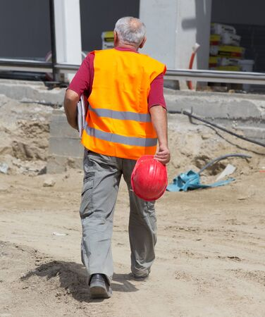 hurrying: Rear view of senior engineer with helmet and blueprints hurrying to construction site Stock Photo