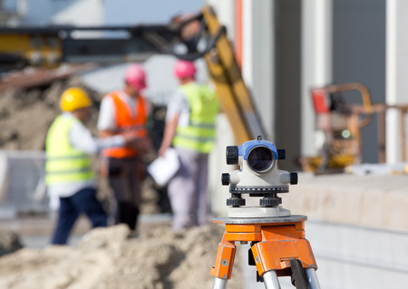 surveying: Surveying measuring equipment level theodolite on tripod at construction site with workers in background