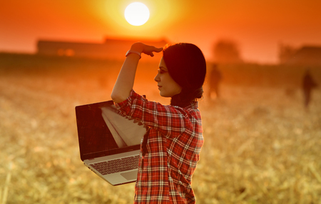 blocking: Young woman with laptop standing in the field and looking in distance in sunset, blocking the sun with hand Stock Photo