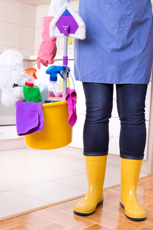 cleaning supplies: Cleaning lady with apron and gumboots holding basket full of cleaning supplies and equipment in front of kitchen