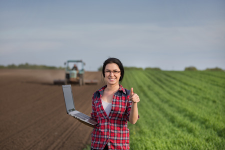 harrowing: Young happy farmer girl standing on field with laptop and showing ok sign with thumb up. Tractor in background Stock Photo