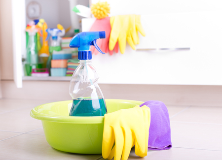 kitchen equipment: Spray bottle and cleaning tools in washbasin on the kitchen floor. Cleaning supplies and equipment stored in kitchen cabinet in background