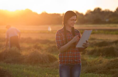 hayfork: Young farmer girl writing notes on field in sunset. Old peasant working with hayfork in background