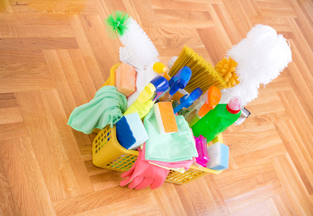 cleaning supplies: Basket full of cleaning supplies and equipment on the parquet