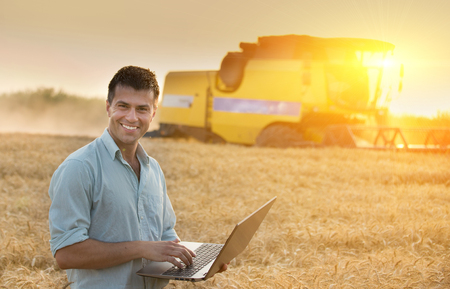 harvest background: Young attractive farmer with laptop in wheat field during wheat harvest. combine harvester working in background