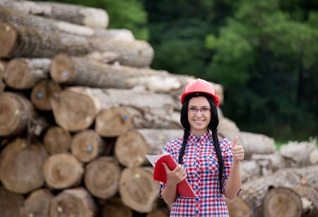 agricultural engineering: Young pretty female lumber engineer standing in front of trunks and showing ok hand sign