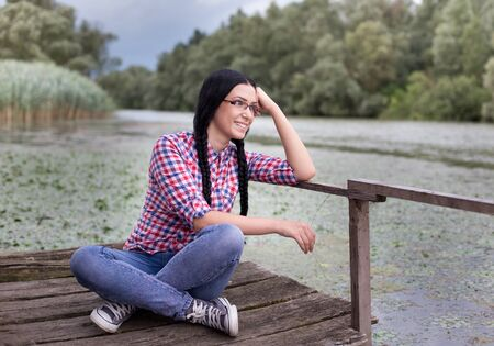 wooden dock: Happy young woman with long braids sitting on wooden dock on the lake