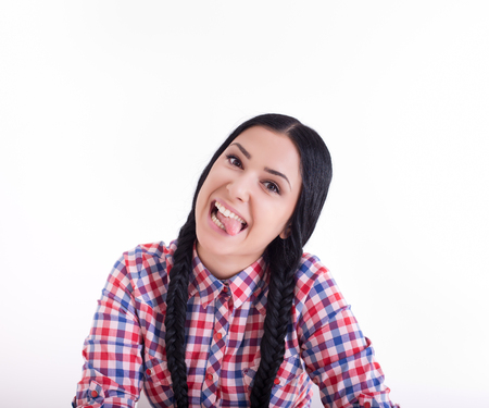freak out: Pretty girl with two braids making silly faces with her tongue out. Isolated on white background