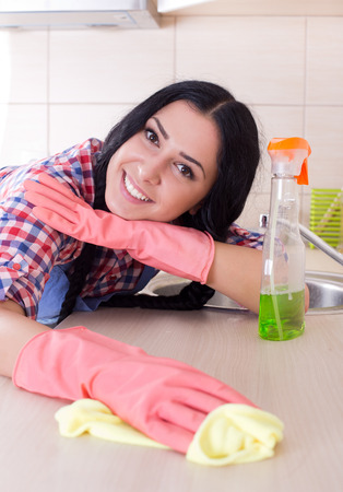 spray bottle: Young pretty woman wiping kitchen countertop with cleaning cloth and spray bottle on counter Stock Photo