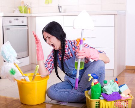 cleaning supplies: Frustrated young woman sitting on kitchen floor with cleaning supplies and equipment and screaming Stock Photo