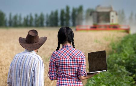 cosechadora: Vista trasera del campesino con sombrero y una mujer joven agricultor con ordenador port�til en el campo de trigo mirando cosechadora
