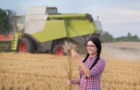 cosechadora: mujer joven busca a los o�dos del trigo en el campo, mientras cosechadora trabaja en segundo plano