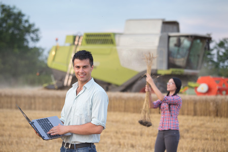 cosechadora: Joven empresario atractivo con el ordenador port�til se coloca en campo y agricultores chica que controla los o�dos del trigo. Cosechadoras de trabajo en segundo plano