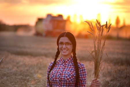 cosechadora: Portrait of young pretty woman with wheat in her hand and combine harvester in background in sunset