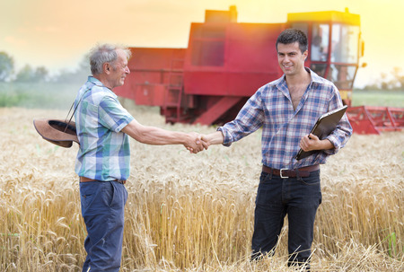 Two farmers shaking hands on wheat field while combine harvesting behind Stockfoto