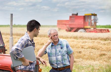 cosechadora: Dos agricultores se inclinan en el tractor y pensando en la soluci�n de problemas en el campo. Cosechadoras de trabajo en segundo plano