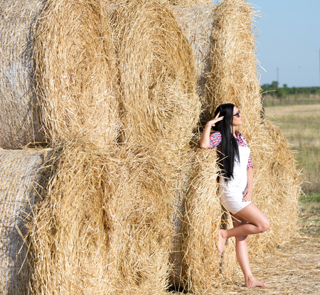 plaid shirt: Beautiful young woman with sunglasses and black long hair in white shorts and plaid shirt standing beside bale of straw in the field and enjoying on sun