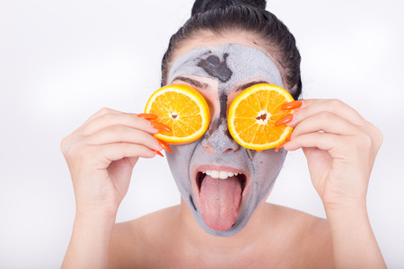 silly face: Pretty young woman making silly face with tongue out while having facial mask and holding two slices of orange on her eyes. Isolated on white background Stock Photo