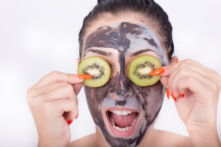 silly face: Pretty young woman with facial mask making silly face with kiwi slices. Isolated on white background