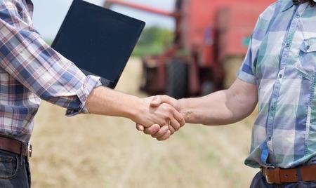 Cerca de dos hombres en camisas de cuadros dándose la mano sobre la tierra de cultivo. Cosechadoras de trabajo en segundo plano