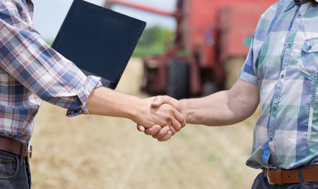 Close up of two men in plaid shirts shaking hands on the farmland. Combine harvester working in background Archivio Fotografico