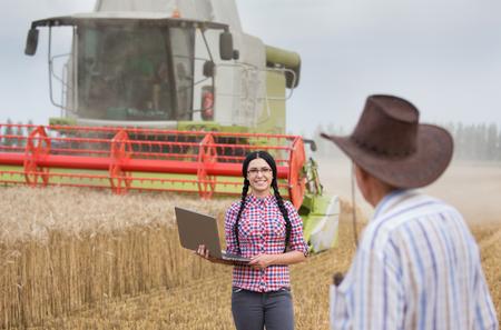 cosechadora: Mujer joven agricultor con la computadora port�til que se coloca delante de la cosechadora en el campo de trigo