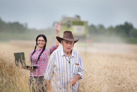 fertile: Senior man and young woman with laptop standing in ripe wheat field