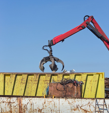 Open grabber throwing out metal scrap over rusty iron waste at junk yard Stock Photo