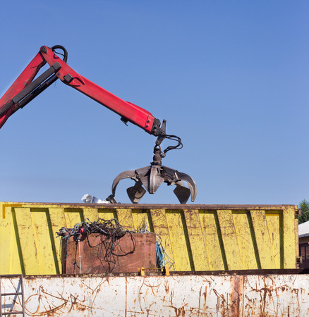 scrap iron: Open grabber throwing out metal scrap over rusty iron waste at junk yard Stock Photo