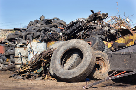 Junk yard full of metal scraps and old used tires and barrels and engine parts. Pollution and recycling concept