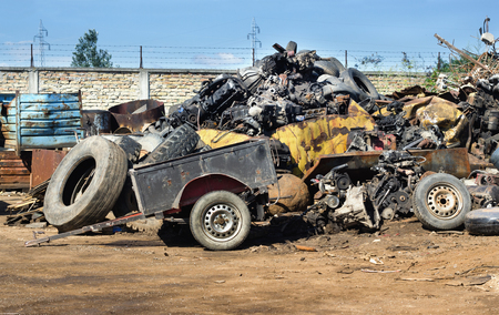 Junk yard full of metal scraps and old used tires and engine parts. Pollution and recycling concept Stock Photo