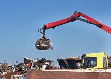 scrap iron: Grabber holding metal scrap over rusty iron waste at junk yard