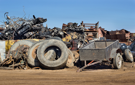 pile reuse engine: Junk yard full of metal scraps and old used tires and engine parts. Pollution and recycling concept Stock Photo
