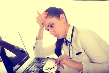 conceived: Conceived business woman holding glasses in one hand and head leaning on other hand over laptop
