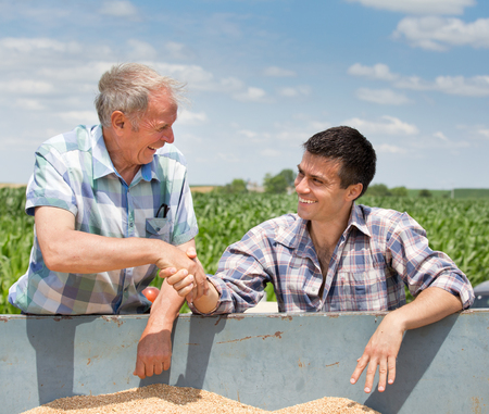 Two farmers shaking hands over trailer full of grains. Agriculture and farming concept 版權商用圖片