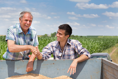 Two farmers shaking hands over trailer full of grains. Agriculture and farming concept Standard-Bild