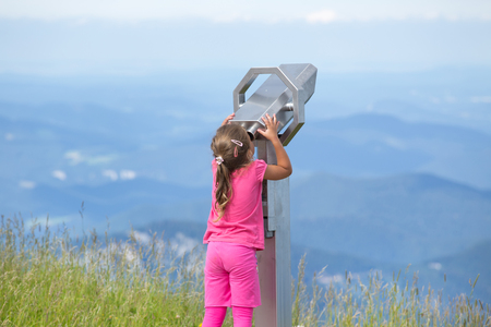 Cute young girl looking through coin operated binoculars from Schneeberg mountain peak in Austria Stock Photo