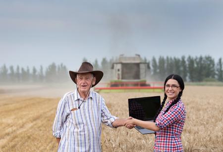 campesinas: Joven empresaria dando la mano a viejo campesino en el campo de trigo en frente de la cosechadora