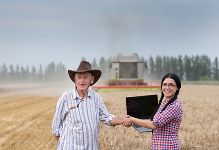 Young businesswoman shaking hands with old peasant on wheat field in front of combine harvester
