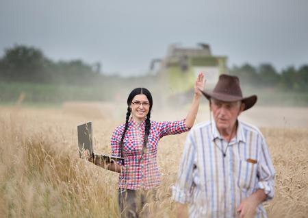 cosechadora: Mujer joven con ordenador port�til agitando la mano al abuelo en campo de trigo, mientras cosechadora trabaja en segundo plano Foto de archivo