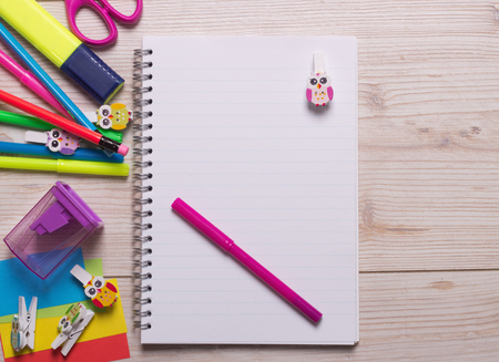 Pink marker and decorative clothespin on notebook and other school supplies on wooden desk. Space for your text Stock Photo