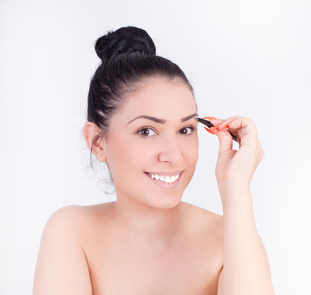 correcting: Pretty young woman correcting eyebrows with tweezers in front of mirror. Beauty and body care concept