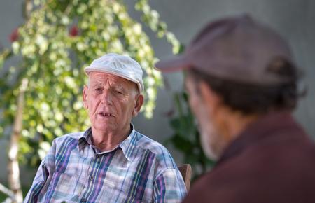 personas escuchando: Dos hombres mayores que hablan en patio en un día soleado